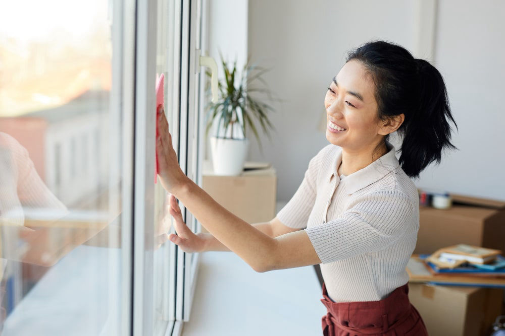 Happy Housekeeper cleaning windows in employer house.
